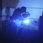 A worker welding a custom basket.