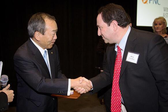 Marlin Steel President Drew Greenblatt greets Takeshi Uchiyamada, chairman of the board of Toyota Motor Corp.