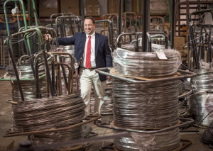 Marlin President Drew Greenblatt next to a stack of steel wire coils