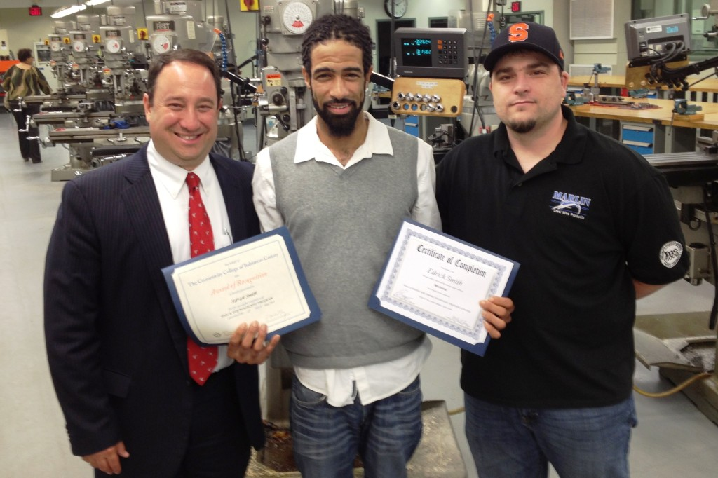 Edrick Smith, a Marlin Steel machinist and new graduate of the Magna Baltimore Technical Training Center, with Marlin Steel President Drew Greenblatt and Marlin Production Manager Andy Croniser