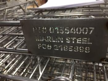 A laser-cut steel sheet tag on a custom wire basket.