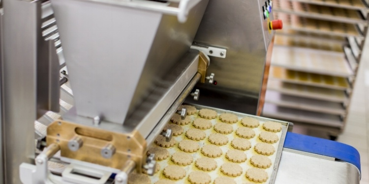 Cookies exiting industrial oven on food grade stainless steel baking tray